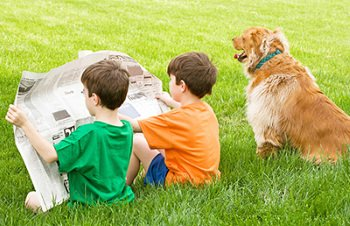 Two boys sitting on the lawn reading the newspaper